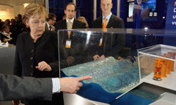 German Chancellor Angela Merkel examines a model of an ocean wave power plant.