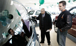 A customer talks with a car salesman at the Apple Chevrolet dealership in Orland Park, Ill.