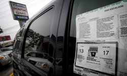 A sticker in the window of a Cadillac Escalade SUV shows EPA estimated mileage figures at Martin Cadillac in Los Angeles.