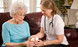 An aide helps an assisted living resident with her medications.