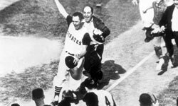 Bill Mazeroski of the Pittsburgh Pirates waves his hand as he walks across home plate to score the winning run of the 1969 World Series against the New York Yankees.