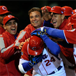 Frederich Cepeda, #24 of Cuba, is mobbed by teammates and team doctor Antonio Castro, top center, son of Fidel Castro, after hitting a three-run home run to end the game against Mexico in the 2009 World Baseball Classic.