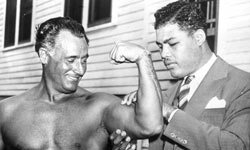World heavyweight champion Joe Louis admires the flexed bicep of Charles Atlas.