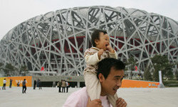 "A man poses with his baby outside of the National Stadium or ""Bird's Nest"" in Beijing. China has experienced a surge in Olympic-themed baby names."