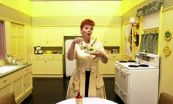 "A Lucy Ricardo impersonator strikes a pose in a recreation of the impossibly clean kitchen set of ""I Love Lucy"" during an exhibition celebrating the 50th anniversary of the TV sitcom."