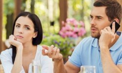 Man talking on cell phone while woman looks mad