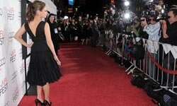Actress Mila Kunis wows the press in an elegant black chiffon dress by Oscar de la Renta.