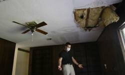 A man wears a mask due to mold growth as he inspects a home in Jupiter, Fla., in April 2008. See more pictures of hidden home dangers.