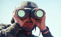 Even with radar, a pair of binoculars still comes in handy for this U.S. soldier during the Gulf War.