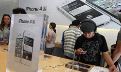 An Apple Store customer looks at the new Apple iPhone 4Gs on October 14, 2011 in San Francisco.