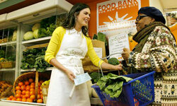 Katie Lee Joel, left, hands fresh produce to West Harlem resident Dorothy White, right, at the Food Bank For New York City's Community Kitchen.