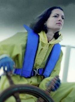 A woman wearing an inflatable life jacket navigates in a storm