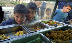 Palestinian kids waiting for their falafel sandwich in East Jerusalem, Israel. The balls of falafel are on the right.