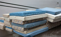 A pile of mattresses wait to be sent through the recycling machine.