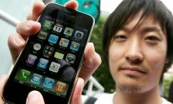 Tetsuya Umeda poses with his new Apple iPhone on the first day of its Japanese launch.