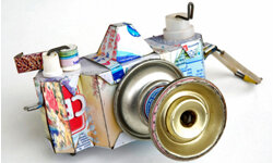 A decorative camera made from recycled materials would be an interesting addition to any bookshelf or side table.