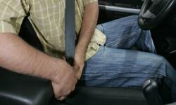 A driver puts on his seatbelt. See more car safety pictures.