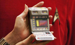 "A Christies New York employee holds a replica of a newer-model tricorder in London on Aug. 2, 2006, as part of a ""Star Trek"" 40th anniversary celebration."