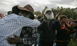 An Aboriginal elder embraces a younger man after Kevin Rudd delivers a formal apology to members of the Stolen Generation.