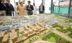 German Chancellor Angela Merkel and Juergen Haepp of Fosters Architecture discuss a model of Masdar City.