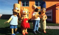 "Bart, Lisa, Homer and Marge show off a full-size replica of ""The Simpsons"" house."
