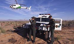 Border Patrol agents work with a helicopter flying overhead to police the border.
