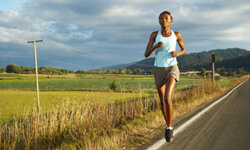 Running down a country road, this runner has a long training run to increase her endurance.