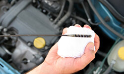 Use the oil change interval recommended by your car's manufacturer to decide when to change the oil, not the color of the oil on the stick.