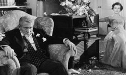 """Actors Spencer Tracy and Joan Bennett collapse in separate chairs in a living room littered with confetti in a still from the film """"Father of the Bride,"""" directed by Vincente Minnelli."""