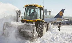 Snow ploughs work to clear snow from a gate area while planes wait.