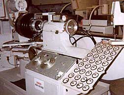 A compound grinder, called a generator, grinds the required curves into the back of the lens blank. The two large dials on the console set the spherical and cylindrical curves that will be ground into the lens.