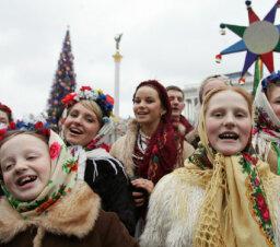 Why do Christmas carolers walk around the neighborhood singing?