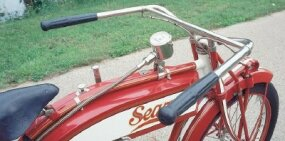 The Deluxe's tank-mounted speedometer was driven off a spiral gear on the rear hub.