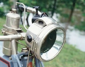 The L-18's headlamp burned acetylene, which was stored in the polished tank mounted behind the handlebars.