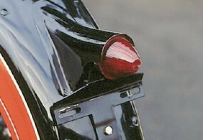 The taillight section of the rear fender was hinged to swing up for tire changes.
