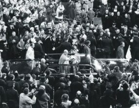 Pope Paul VI waves to an applauding crowd while riding in a specially modified Lehmann-Peterson limousine during his visit to New York City in October 1965.