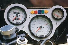 The aluminum gauge panel is dominated by a large tachometer redlining at 8000 rpm.