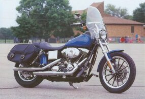 The standard 2002 Harley-Davidson FXDL Dyna Lowrider has accessory saddle bags and windshield.