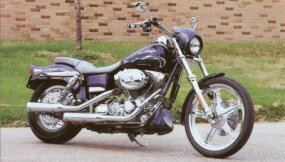 The 2002 Harley-Davidson FXDWG3 features custom grips, mirror stalks, and forward-mounted foot controls.