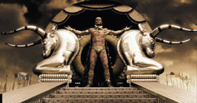 Xerxes (Rodrigo Santoro), the Persian king who claims to be a god, stands atop his elaborate golden litter.