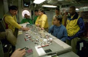 "Crew members on the USS George Washington circle around the ""Ouija Board."""