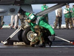 A member of the USS George Washington flight-deck crew checks an F-14 Tomcat's catapult attachment.