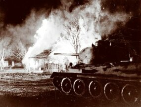 A Russian T-34 tank rolls through a burning village during the battle of Kursk in July 1943.