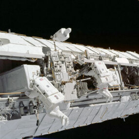 Astronauts install a truss, which was delivered to the space station by Endeavour (STS113).