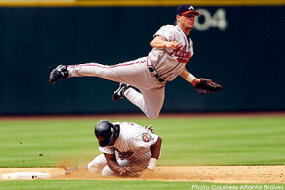 Former Atlanta Braves second baseman Marcus Giles leaps over an opposing player to complete a double play.