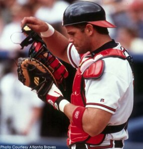 Former Atlanta Braves catcher Javy Lopez adjusts his chest protector and helmet.