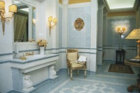 This Italian-villa style bath has border tiles in a Greek key motif and corbel-style supports for the sink.