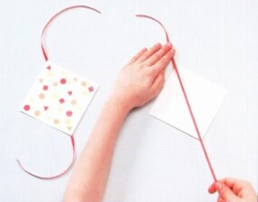 On the unstamped side, spread a diagonal line of glue and affix the ribbon.