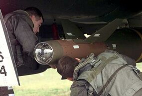 An F-15E Strike Eagle pilot and a weapons system officer inspect a GBU-28 laser-guided bomb.