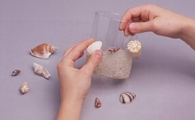 Decorate the glass with sand and shells.